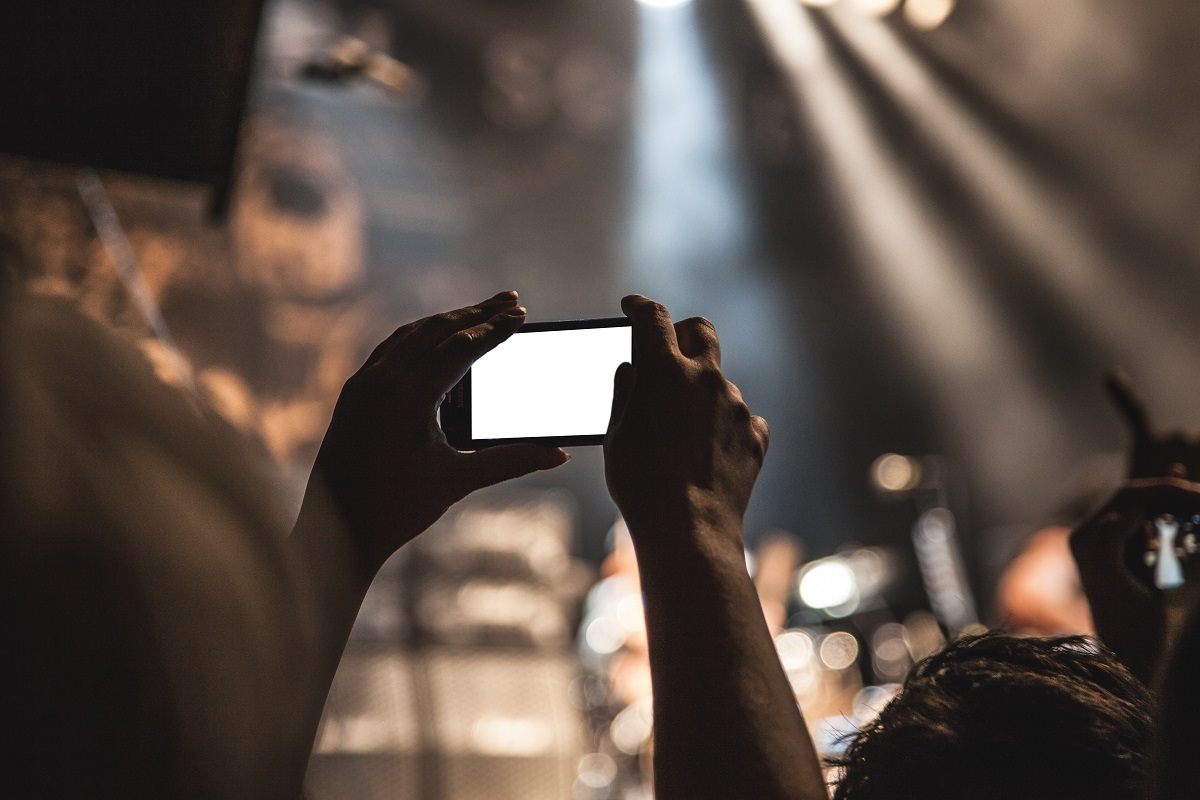 a festival goer taking a picture with their phone at Austin City Limits 2015