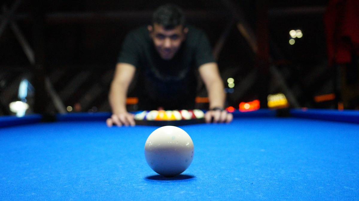 photo; pool player hovering over a pool table